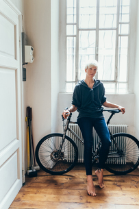 Woman sitting on bicycle at homeの写真素材 [FYI03609801]
