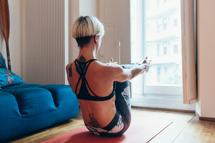 Woman practising yoga at homeの写真素材 [FYI03609809]