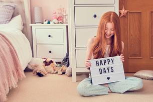 Girl holding up sign on bedroom floorの写真素材 [FYI03609921]