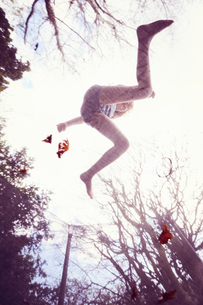 Girl jumping on trampoline, low angle viewの写真素材 [FYI03609934]