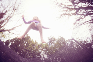 Girl jumping on trampoline, low angle viewの写真素材 [FYI03609936]