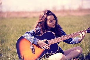 Girl playing guitar on grassの写真素材 [FYI03609940]