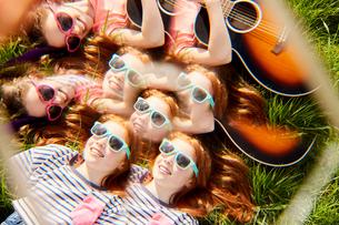 Girls playing guitar on grassの写真素材 [FYI03609958]
