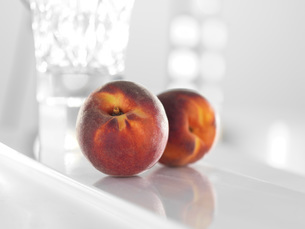 Peaches on glossy white surfaceの写真素材 [FYI03610204]