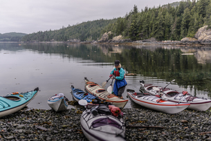 Woman with sea kayaks on lakeside, Johnstone Strait, Telegraph Cove, Canadaの写真素材 [FYI03610378]