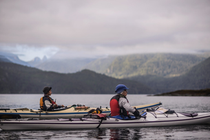 Friends kayaking in lake, Johnstone Strait, Telegraph Cove, Canadaの写真素材 [FYI03610382]