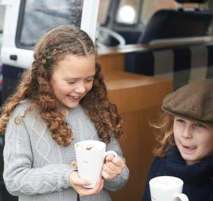Girls drinking hot chocolate beside camper vanの写真素材 [FYI03610427]