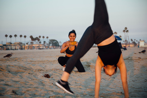 Friends photographing exercise on beach, Long Beach, California, USの写真素材 [FYI03610634]