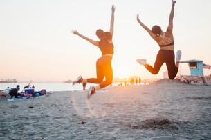 Friends jumping on beach, Long Beach, California, USの写真素材 [FYI03610635]