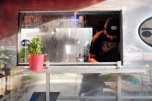 Man cooking in camper van food truckの写真素材 [FYI03610710]