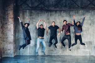 Colleagues in jumping pose for group photo against concrete wallの写真素材 [FYI03610823]