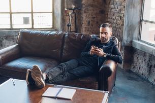 Man on sofa using smartphoneの写真素材 [FYI03610852]