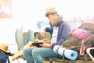 Young couple in departure lounge at airport, woman resting head on man's legs, man using digital tabの写真素材 [FYI03610928]