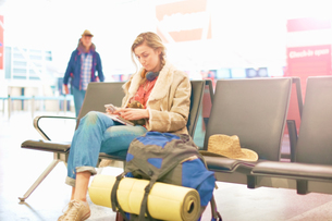 Young woman at airport, sitting with backpack beside her, using smartphoneの写真素材 [FYI03610930]