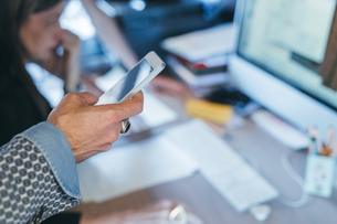 Man using cellphone at deskの写真素材 [FYI03610976]