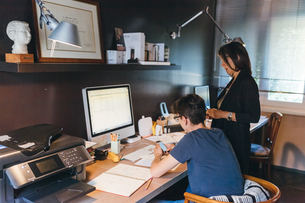 Woman and son working in home officeの写真素材 [FYI03610991]