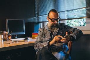 Man using cellphone at deskの写真素材 [FYI03610993]