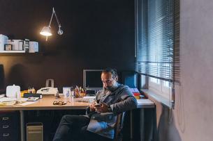 Man using cellphone at deskの写真素材 [FYI03610994]
