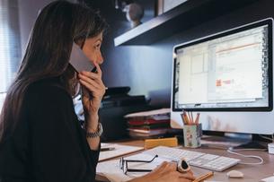 Woman using cellphone at desktopの写真素材 [FYI03610996]