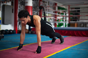 Female boxer doing planks in gymの写真素材 [FYI03611021]