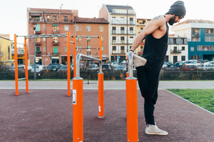 Man using parallel bars in outdoor gymの写真素材 [FYI03611028]