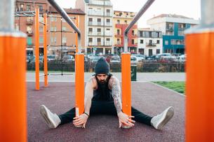 Man using parallel bars in outdoor gymの写真素材 [FYI03611030]