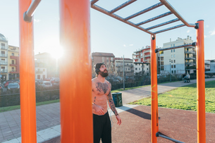 Man contemplating horizontal ladder in outdoor gymの写真素材 [FYI03611058]