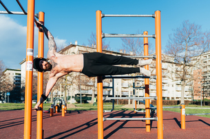 Man using horizontal ladder in outdoor gymの写真素材 [FYI03611059]