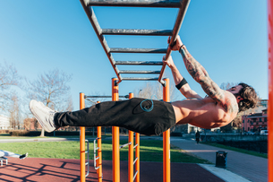 Man using horizontal ladder in outdoor gymの写真素材 [FYI03611060]