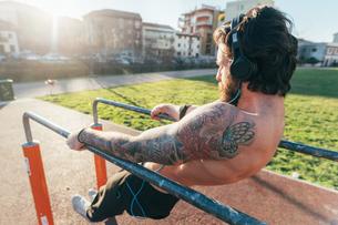 Man using parallel bars in outdoor gymの写真素材 [FYI03611062]