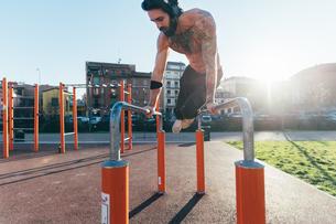 Man using parallel bars in outdoor gymの写真素材 [FYI03611064]