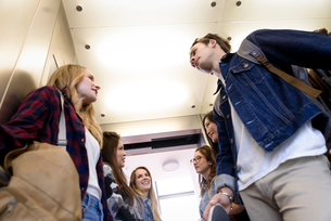 University students talking inside elevatorの写真素材 [FYI03611101]