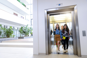 University students exiting elevator in campusの写真素材 [FYI03611108]