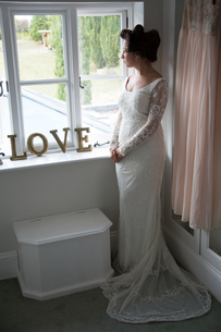 Bride looking out of window before weddingの写真素材 [FYI03611139]