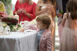 Boy curious about gifts and cake at wedding receptionの写真素材 [FYI03611170]