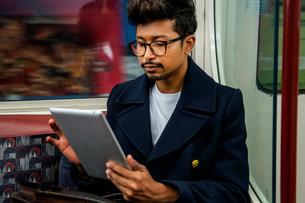 Businessman using digital tablet inside trainの写真素材 [FYI03611193]