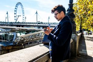 Businessman using smartphone on Embankment, London Eye and Hungerford Bridge in background, London,の写真素材 [FYI03611195]