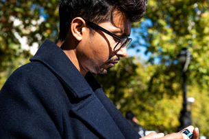 Businessman using smartphone outdoorsの写真素材 [FYI03611197]