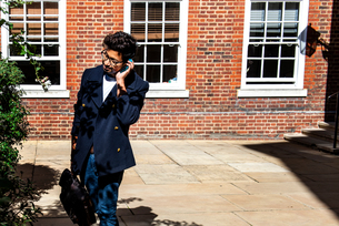 Businessman using smartphone in front of buildingの写真素材 [FYI03611200]