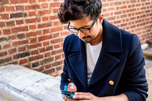 Businessman using smartphone in front of buildingの写真素材 [FYI03611204]