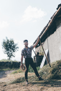 Young male agricultural worker with pitchfork, full length portraitの写真素材 [FYI03611290]