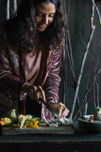 Young woman chopping fresh food on rustic cutting boardの写真素材 [FYI03611325]