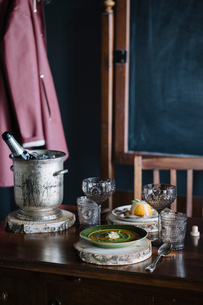 Bowl of fresh garnished soup, a dessert and champagne on vintage tableの写真素材 [FYI03611335]