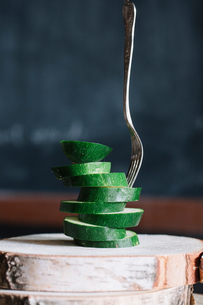 Stacked sliced courgettes and fork on rustic cutting boardの写真素材 [FYI03611354]