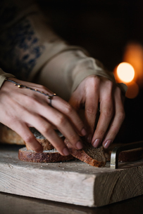 Young woman preparing brown bread on rustic chopping board, close up of handsの写真素材 [FYI03611368]