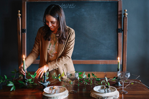 Young woman decorating vintage dinner table with candle and foliageの写真素材 [FYI03611373]