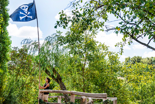 Boy on tree house with pirate flagの写真素材 [FYI03611473]