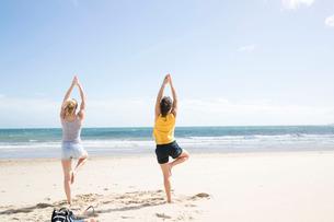 Sisters enjoying yoga on beachの写真素材 [FYI03611581]