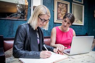 Women brainstorming business ideas in restaurantの写真素材 [FYI03611583]