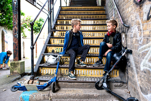Twins talking on metal staircaseの写真素材 [FYI03611743]